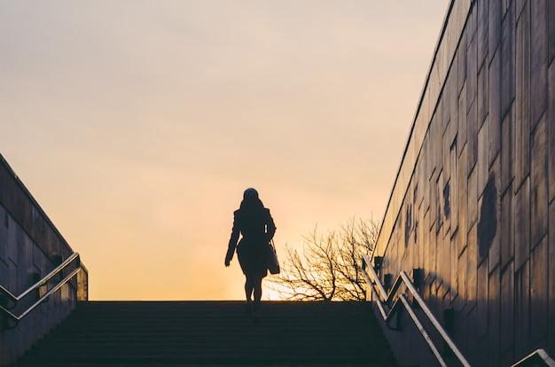 Silhouet van een vrouw die uit een onderdoorgang komt. stadsleven