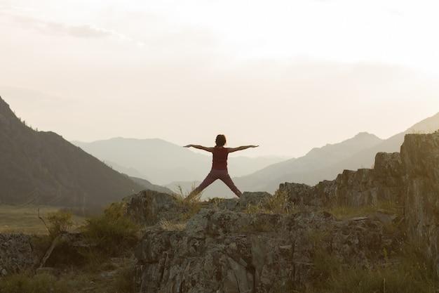 Silhouet van een vrouw die yoga of qigong doet in de bergen bij zonsondergang in de zomer