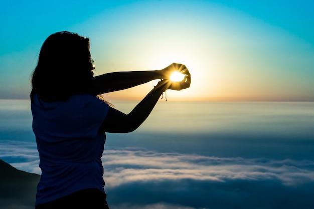 Silhouet van een vrouw die zonnebaadt met haar handen op de top van een berg