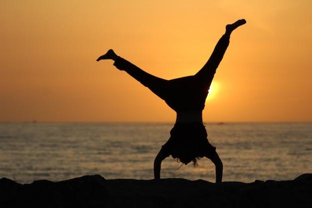 Silhouet van een vrouw doet een radslag met een wazige zee en een heldere hemel