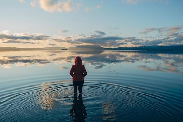 Silhouet van een vrouw op haar rug in een rustig meer waar de wolken en de blauwe lucht