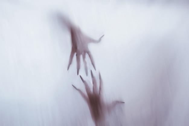 Silhouet van een vrouwelijk seksueel figuur achter mistig glas. concept van de geest van poltergeist uit de andere wereld. beangstigende handen van de dood door het weefsel.