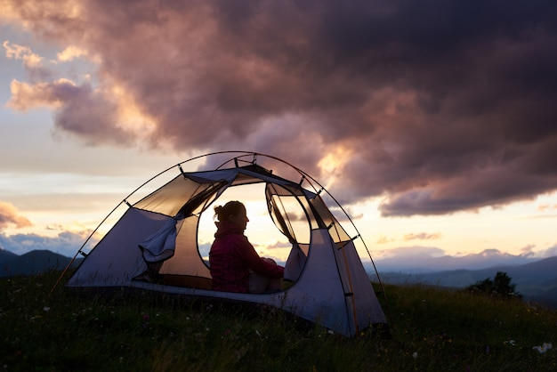 Silhouet van een vrouwelijke camper in de bergen op zonsondergang
