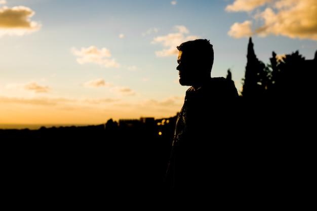 Silhouet van eenzame jonge man staat op de berg en kijkt in de verte