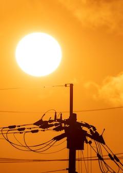 Silhouet van elektriciteitspost met grote zon