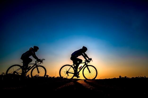 Silhouet van fietser op zonsondergangachtergrond.