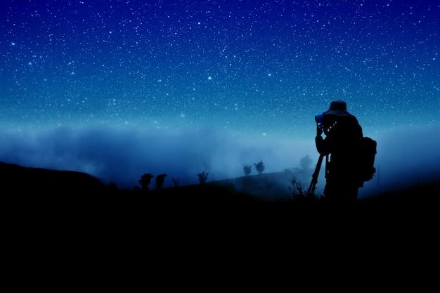 Silhouet van fotograaf die nachtsterren schieten