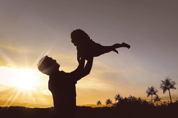 Silhouet van gelukkig vader en meisje die samen spelen