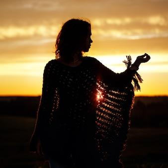 Silhouet van gelukkige jonge vrouw op zonsondergang, buitenmeisje in een geruite poncho in een veld met aartjes