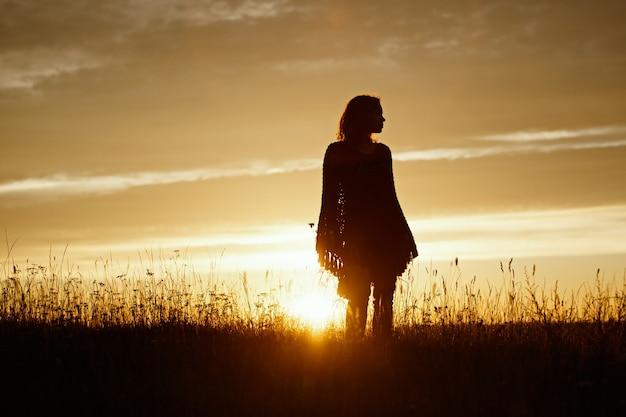Silhouet van gelukkige jonge vrouw op zonsondergang, buitenmeisje in een geruite poncho