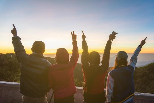 Silhouet van gelukkige mensen die hun handen met een zonachtergrond opheffen.