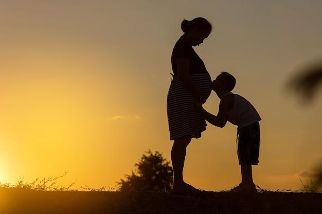 Silhouet van gelukkige pragnancy moeder met zijn zoon die in zonsondergang speelt