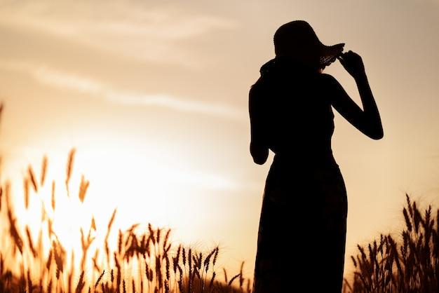 Silhouet van gelukkige vrouw in een tarweveld bij zonsondergang