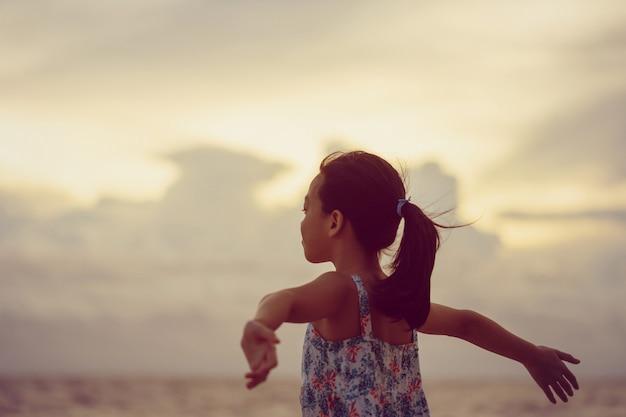Silhouet van genieten van klein meisje op het strand, kid ontspannen in de zomer avondrood buiten