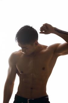 Silhouet van gespierde aziatische man binnenshuis