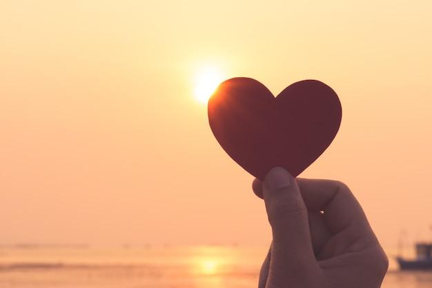 Silhouet van hand die rood hart houdt tijdens zonsondergangachtergrond.