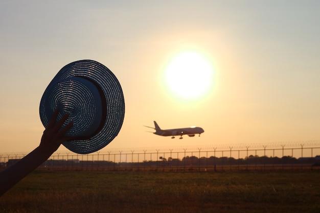 Silhouet van hand met hoed zwaaiend naar het vliegtuig dat naar de zonsopgang vliegt