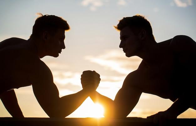 Silhouet van handen die concurreren in kracht.