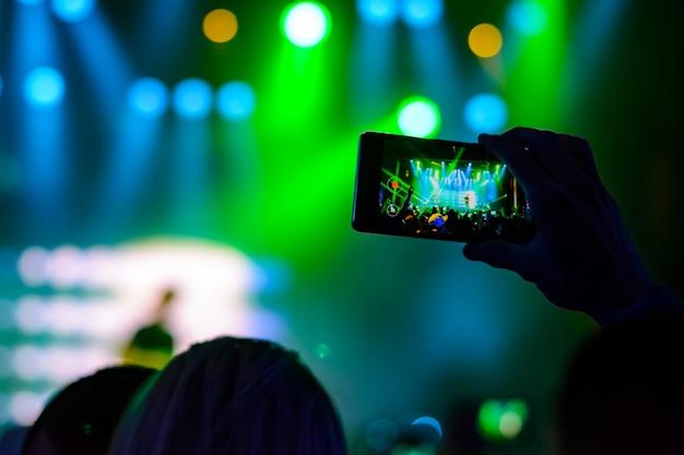 Silhouet van handen met een smartphone tijdens een concert
