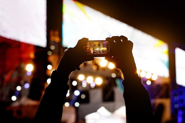 Silhouet van het gebruik van een mobiele telefoon tijdens een concert.