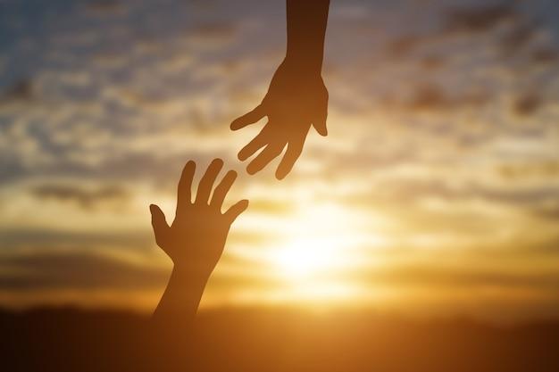 Silhouet van het geven van een helpende hand, hoop en steun elkaar op zonsondergangachtergrond.
