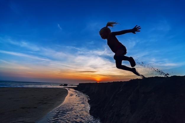 Silhouet van het jonge meisje dat hoog in de lucht springt vanaf een zanderige klif op het zonsondergangstrand, kleurrijke hemel