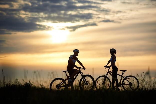 Silhouet van het paar met fietsen