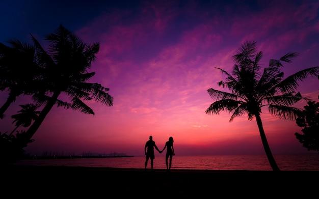 Silhouet van het paar op tropisch strand tijdens zonsondergang op de achtergrond van palmen