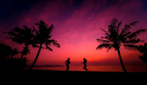 Silhouet van het paar op tropisch strand tijdens zonsondergang op de achtergrond
