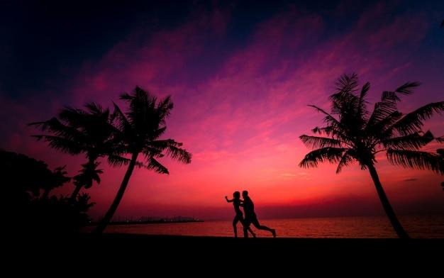 Silhouet van het paar op tropisch strand tijdens zonsondergang