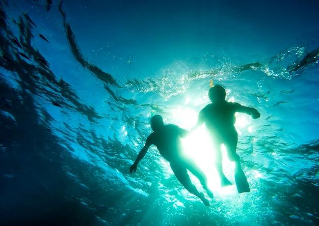 Silhouet van hoger paar dat samen in tropische overzees zwemt