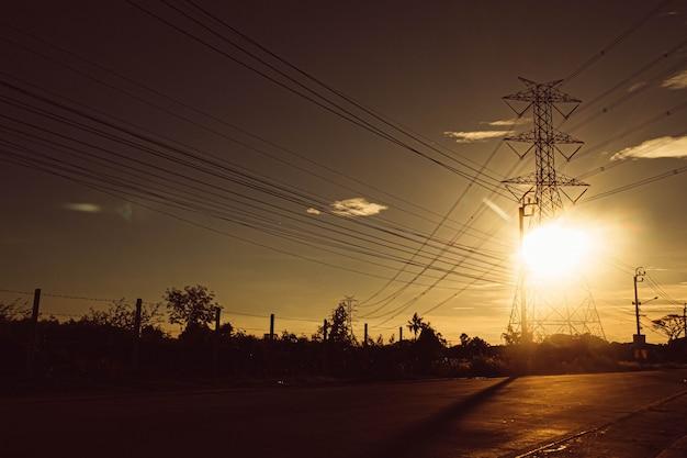 Silhouet van hoogspanningstoren met elektrische draden op zonsondergangachtergrond. uitzicht door het gras. power line-ondersteuning in een veld met ondergaande zon hoogspanningsleidingen bij zonsondergang, hoogspanning