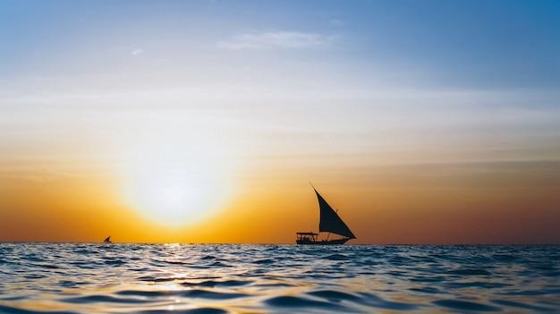 Silhouet van jacht in de open oceaan op de zonsondergang