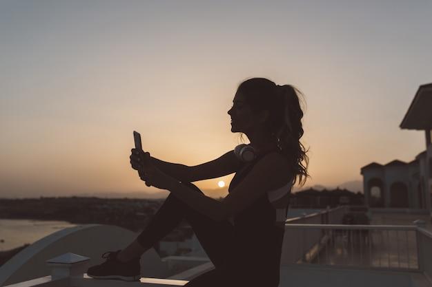 Silhouet van jonge aantrekkelijke vrouw in sportkleding selfie maken aan de kust op zonsondergang. positiviteit, actieve levensstijl, genieten, opgewekte stemming uitdrukken.