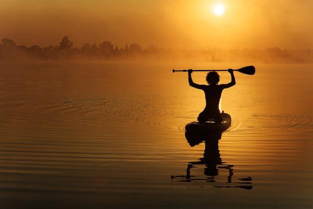 Silhouet van jonge actieve sportman zwemmen op paddle board op lokaal meer.