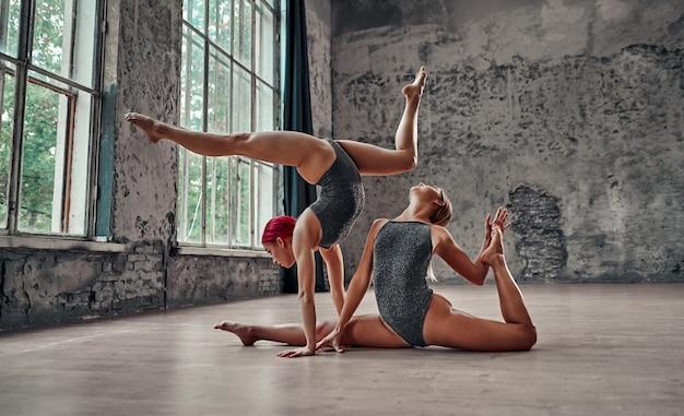 Silhouet van jonge coole aantrekkelijke yogi-vrouw die yogaconcept beoefent, staande in adho mukha vrksasana-oefening, naar beneden gerichte boomhouding en een ander meisje zit in touw.