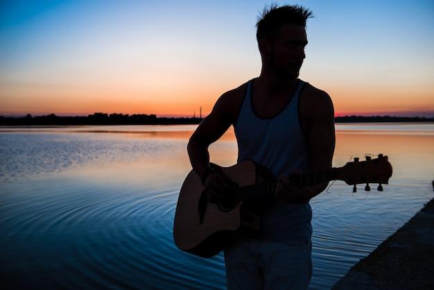 Silhouet van jonge knappe man gitaarspelen op zee tijdens zonsopgang
