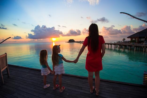 Silhouet van jonge moeder en twee haar kleine meisjes bij zonsondergang