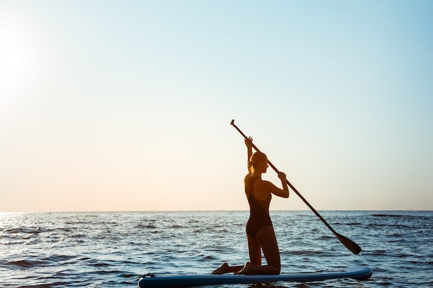 Silhouet van jonge mooie vrouw surfen in zee bij zonsopgang.