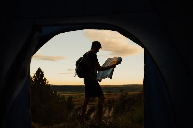 Silhouet van jonge toerist die een kaart dichtbij zijn tent bij bergen onderzoekt.
