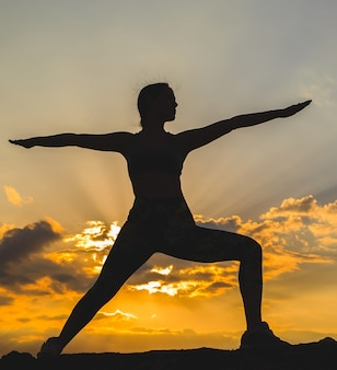 Silhouet van jonge vrouw het beoefenen van yoga of pilates bij zonsondergang of zonsopgang in een prachtige berglocatie.