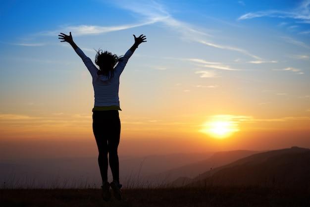 Silhouet van jonge vrouw springen