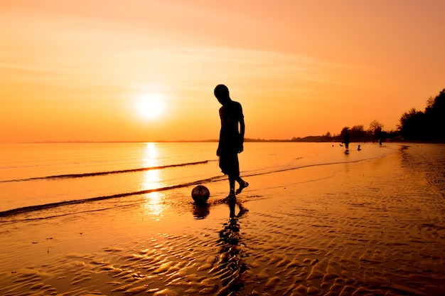 Silhouet van jongen het spelen op het strand met zonsonderganghemel