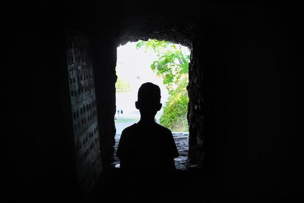 Silhouet van jongen in het raam van fort, uitzicht vanuit het donker