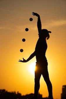 Silhouet van jongleur met ballen op kleurrijke zonsondergang.