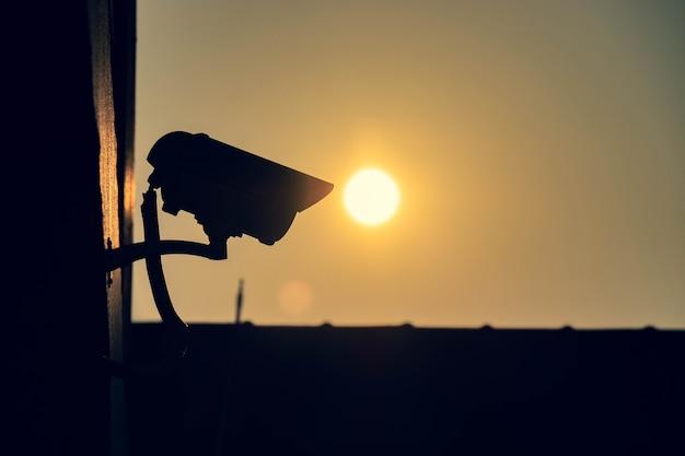 Silhouet van kabeltelevisie-beveiligingscamera buiten het inbouwen van de ochtend met zonachtergrond