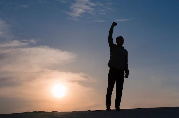 Silhouet van kerel met handen omhoog in zonsondergangtijd op hemel
