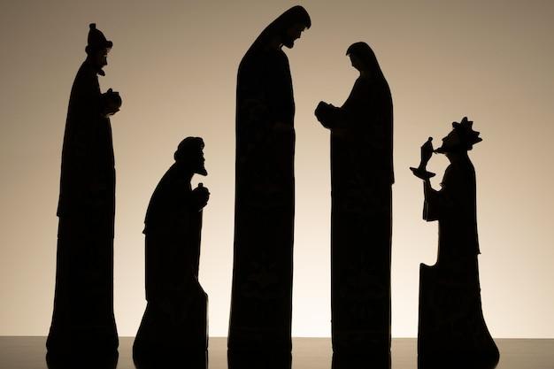 Silhouet van kerststal met baby jezus op de schoot van maria, met jozef en de drie wijze mannen