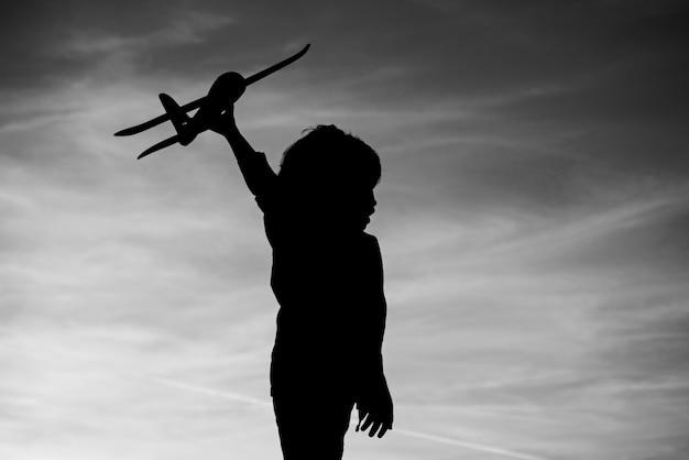 Silhouet van kind met speelgoed vliegtuig in de hand