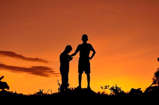 Silhouet van kinderen die in het bos met zonsonderganghemel spelen